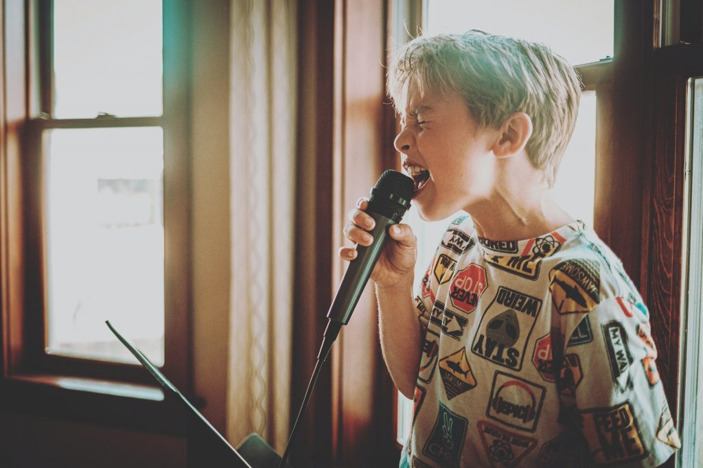 Young boy singing at home